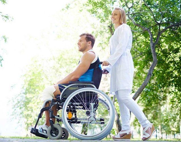 Mladá žena tlačí muža na vozíku
